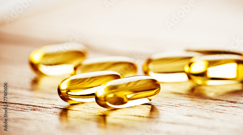 Fish oil omega 3 gel capsules  on wooden background - 77461606