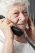 pensive elderly woman calling on the phone - 77462463