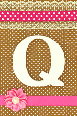 Wooden letter Q on polka dots background