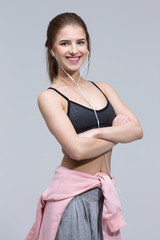 Portrait of a beautiful sporty woman over gray background