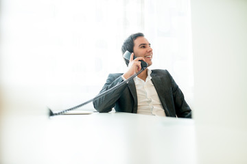 Successful happy businessman talking on a phone