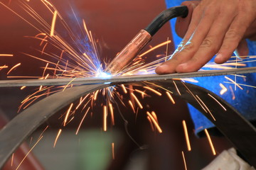 welder is welding steel flat bar without safety glove