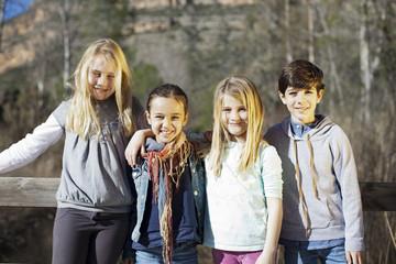 Niños apoyados sobre barandilla en el campo