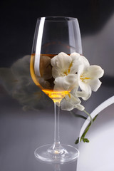 Double exposure of glass of wine over white freesia