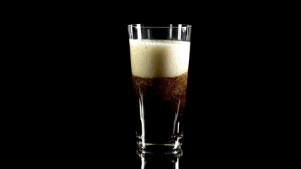 Glass of coke with large foam at the top