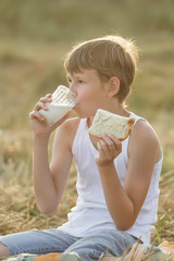 Teenage farmer boy enjoying fresh milk and bread