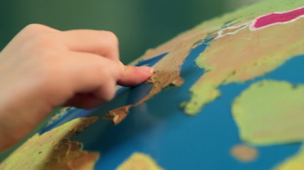 Close up of a small hand showing on a Earth globe