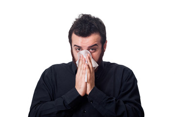 Man blowing his nose in a tissue