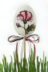 Easter egg painted with a flower with bows in the grass.
