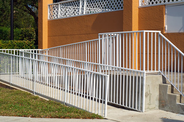 handicap ramp with white railing and orange wall