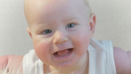 Happy baby looks into the camera
