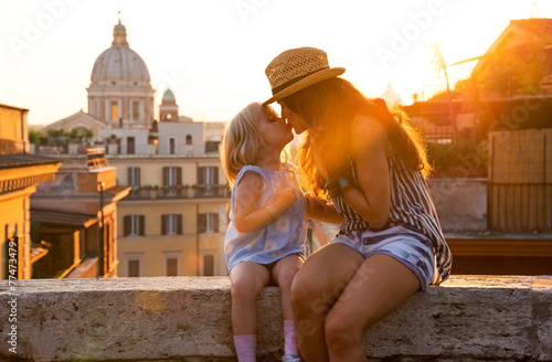 Fototapeta Mother and baby girl kissing while sitting on street in Rome