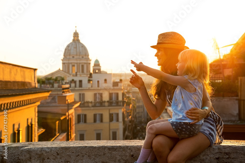 Fototapeta Mother and baby girl sitting on street in Rome