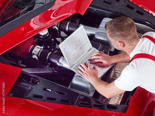 Leinwanddruck Bild Mechanic is tuning and checking the engine