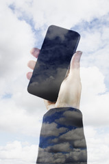 Female hand holding a smart phone surrounded by clouds