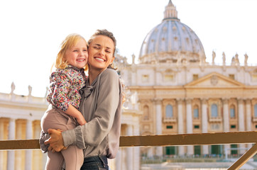 Portrait of happy mother and baby girl hugging in Vatican