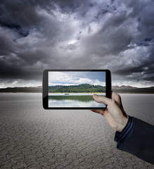 Hand holding a digital tablet in a desert