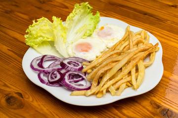 Uova e patatine fritte con contorno di cipolle rosse e lattuga