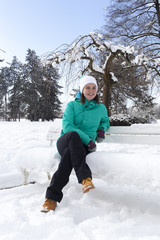 Cute young woman sitting on a snowy bench