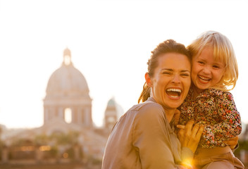 Portrait of happy mother and baby girl against rome panorama