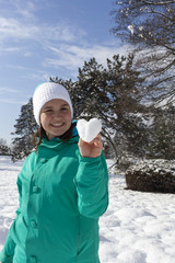 Lovely young woman showing snow heart