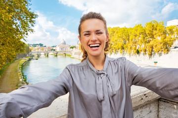 Smiling young woman making selfie on bridge ponte umberto I