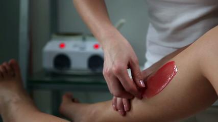 Woman having her legs waxed in beauty salon