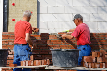 Bricklayers work together as a team
