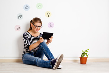 Happy girl sitting on the floor using tablet pc for chatting