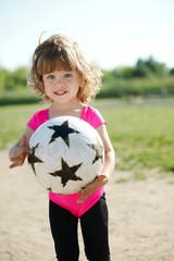 little girl plays football on stadium