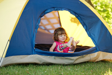 little girl sitting in colorful tent