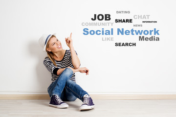 Smiling girl on the floor pointing on social network chart