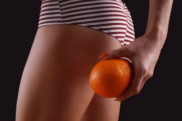 Frau hält Apfelsine an den Po