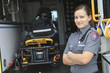 Leinwanddruck Bild - Paramedic employee with ambulance in the background.