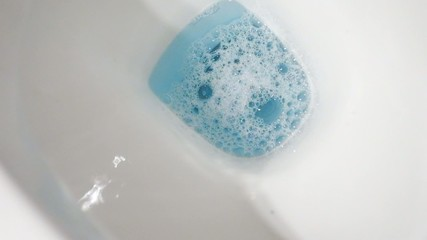 Blue water in the white toilet bowl full HD footage