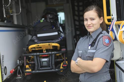 Leinwanddruck Bild Paramedic employee with ambulance in the background.
