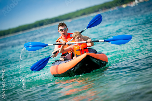 father and son in a kayak - 77479821