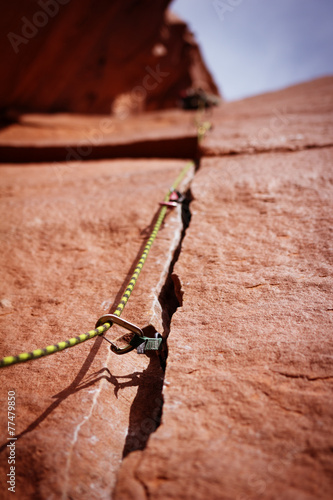 Fototapeta Rock climbing gear in crack