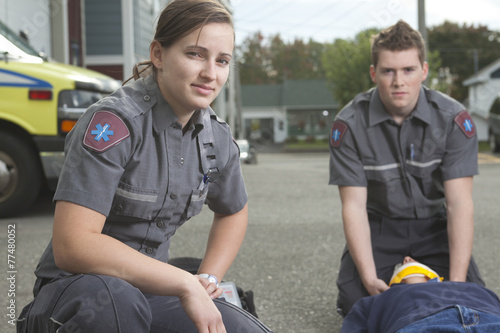 Paramedic employee with ambulance in the background. - 77480052