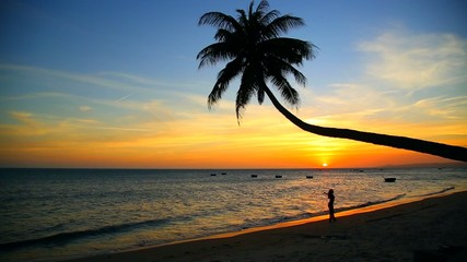 Young girl walking on a tropical beach at sunset