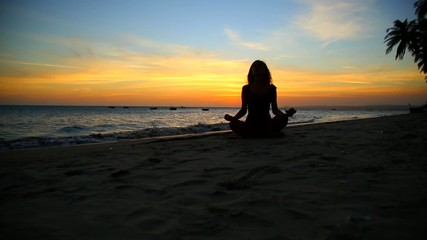 young girl practicing yoga by the sea at sunset
