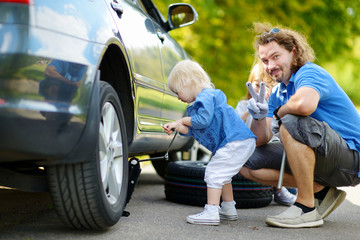 Little girl helping father to change a car wheel