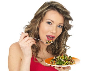 Young Woman Eating an Aromatic Rainbow Asian Style Salad