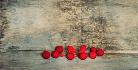 red felted beads and boots on the wooden background