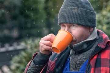 Mann in einer warmen Jacke macht Pause und trinkt Kaffee