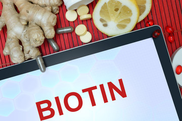 Tablet with word Biotin. Healthy eating.