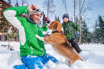 Father with son playing with their dog in deep snow