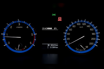 Backlit gauges of an automobile. Blue glowing meters with a whit