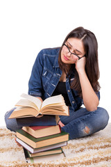 girl student sitting with a pile of books