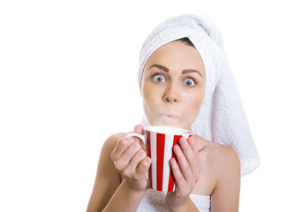 Funny woman wrapped in a towel drinking hot tea